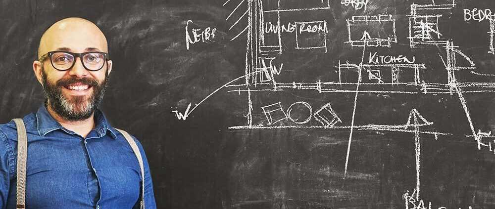 architect man sketching new project on chalkboard PHJS8QE